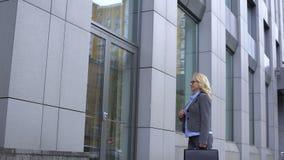 Político fêmea feliz que admira a reflexão no vidro do prédio de escritórios, carreira filme