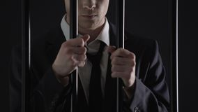 Político que sostiene las barras de la prisión, varón oficial arrestado en blanqueo de dinero almacen de video