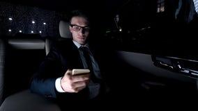 Político que usa el teléfono en asiento trasero del coche de lujo como conducción del hogar, trabajoadicto imagen de archivo libre de regalías