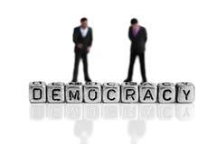 Políticos miniatura del modelo de escala que se colocan detrás de la democracia de la palabra Foto de archivo libre de regalías