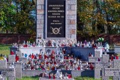 POLÔNIA, Koscian novembro, 5, 2017; muitas velas na sepultura de mármore no cemitério imagens de stock royalty free