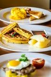 Polędwica stek nakrywający z smażyć jajecznymi i śniadaniowymi grulami, miękka część gramolił się jajka z uwędzonym łososiem Słuz Fotografia Royalty Free