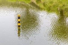 Pol för vattennivå som indikerar vattendjup av den naturliga sjön i summe Royaltyfri Fotografi