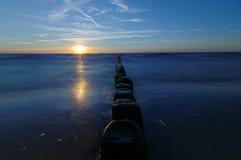 Polônia, Báltico Por do sol sobre o mar Quebra-mar na superfície lisa do mar Imagem de Stock