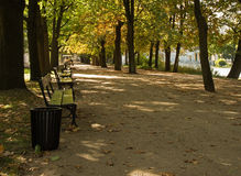 Poland.Alley in a park with a row of benches in autumn.horizonta Royalty Free Stock Image