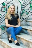 A poland blonde young woman, 24 years, sitting on marble stairs, looking camera, smiling, outdoors. Portrait of a blonde poland young woman, 24 years, sitting on royalty free stock photo