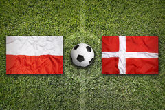Poland and Denmark flags on soccer field Royalty Free Stock Photography