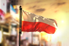 Poland Flag Against City Blurred Background At Sunrise Backlight Stock Photos