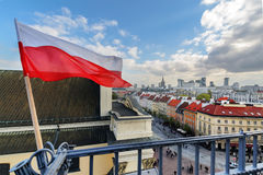 Poland Flag in Blue Sky and Warsaw in background Stock Images