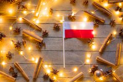Poland flag and Christmas lights around. On wooden background Stock Images