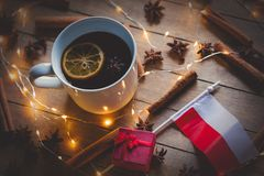 Poland flag and cup tea with Christmas ingredients. On wooden background Royalty Free Stock Photos