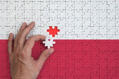 Poland flag is depicted on a puzzle, which the man`s hand completes to fold.  stock illustration