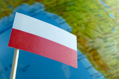 Poland flag with a globe map as a background. Macro stock image