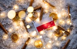 Poland flag and lemons with cinnamons. On snow backgroud and Fairy lights Royalty Free Stock Photo