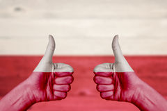Poland flag painted on female hands thumbs up. With blurry wooden background Stock Photos