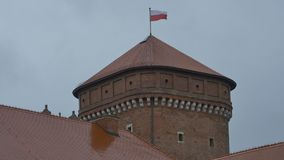 Poland Flag on Tower. The flag of Poland waving on a grey sky on a medieval tower stock video footage