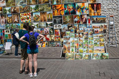 POLAND, KRAKOW - MAY 27, 2016: Tourists admires the outdoor gallery paintings for sale near the city walls at St. Florian Gate. stock photography