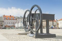 Poland, Malopolska, Oswiecim, Market Square. Sunlit, replica of an ancient well royalty free stock photo