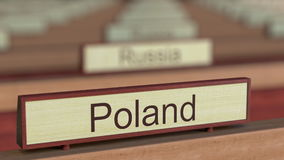 Poland name sign among different countries plaques at international organization. 3D rendering Stock Images