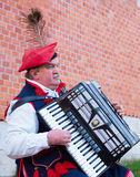 Poland traditional busker. KRAKOW, POLAND - NOV 11, 2014: Street musician wore in traditional Poland dress playing on the street of Krakow Royalty Free Stock Image