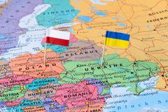 Poland and Ukraine map with flag pins, political relations concept image. Flag pins of Poland and Ukraine on a world map, political relations concept image Royalty Free Stock Images