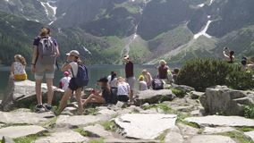 Poland, Zakopane,Tatras June 2019. Tourists on the shore of the mountain lake sea eye.  stock footage