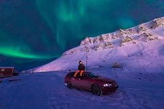 The polar arctic man Northern lights aurora borealis sky star in Norway Svalbard in Longyearbyen city moon mountains. The polar arctic man Northern lights aurora Stock Photography