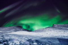 The polar arctic Northern lights aurora borealis sky star in Norway Svalbard in Longyearbyen city moon mountains. The polar arctic Northern lights aurora Stock Images
