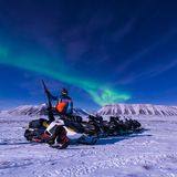 The polar arctic snowmobile  Northern lights aurora borealis sky star in Norway Svalbard in Longyearbyen city man mountains. The polar arctic man Northern lights Royalty Free Stock Photos