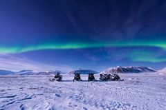 The polar arctic snowmobile Northern lights aurora borealis sky star in Norway Svalbard in Longyearbyen city moon mountains. The polar arctic man Northern lights royalty free stock image