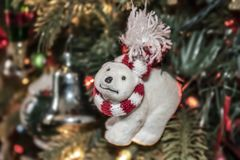 Polar bear Christmas ornament with red & white scarf and crooked nose and funny expression against bokeh decorated tree withh ligh. Ts - selective focus royalty free stock images