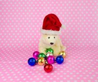 Polar bear doll wearing a Santa hat with Christmas balls. Royalty Free Stock Photos