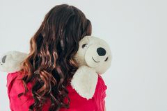 Polar bear toy hugs young curly brunette woman in bright pink dress royalty free stock photo