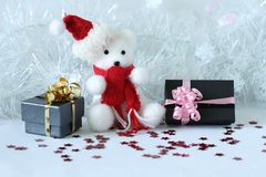 Polar bear wearing a hat and a blue scarf posed next to gifts with shiny knots on a Christmas holiday decor. A polar bear wearing a hat and a blue scarf posed Stock Photo