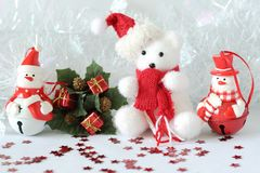 Polar bear wearing a hat and a blue scarf posed next to gifts with shiny knots on a Christmas holiday decor. A polar bear wearing a hat and a blue scarf posed Stock Image