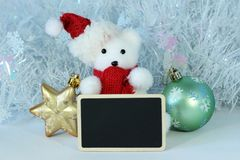 Polar bear wearing a hat and a red scarf for Christmas party decoration with a empty message slate Royalty Free Stock Images