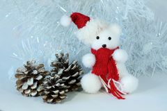 Polar bear wearing a hat and a red scarf posed next to gifts with shiny knots on a Christmas holiday decor. A polar bear wearing a hat and a red scarf posed next Royalty Free Stock Photos
