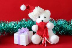 Polar bear wearing a hat and a red scarf posed next to gifts with shiny knots on a Christmas holiday decor. A polar bear wearing a hat and a red scarf posed next Stock Photography