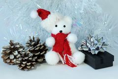 Polar bear wearing a hat and a red scarf posed next to gifts with shiny knots on a Christmas holiday decor. A polar bear wearing a hat and a red scarf posed next Stock Photo
