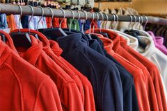Polar fleece jackets. Fleece jackets hanging on clothes hangers stock photo