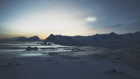Polar night above arctic snow mountain aerial view. Sunrise in antarctic winter ocean open water glacier. Beautiful sky horizon landscape top drone flight stock video footage