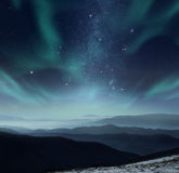 Polar night. Starry night sky with aurora polaris over the mountains Royalty Free Stock Photo