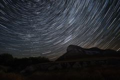 Polar Star at the center of rotation. Beautiful star trails time-lapse over the hills. Lateral light from the full moon on the chalk hills. Cretaceous Hills Royalty Free Stock Image