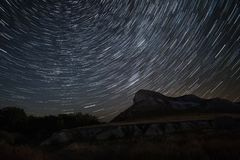 Beautiful star trails time-lapse over the hills. Polar North Star at the center of rotation. Polar Star at the center of rotation. Lateral light from the full Royalty Free Stock Photography