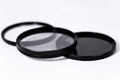 Polariser, UV, neutral density on white. A still-life of the most popular photographic filters on white stock photo