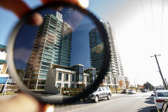 Polarizing filter held in front of a camera lens Stock Photography