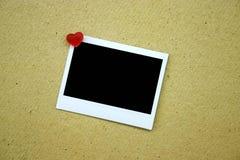 Polaroïd blanc goupillé sur le mur Photographie stock libre de droits