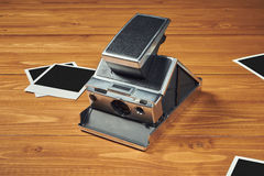 Polaroid camera and film. On wood table Stock Photo