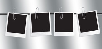 Polaroid Film Frame. A set of four Polaroids film frames fixed to a washing line with four paper clips on a graduated Grey background Stock Image
