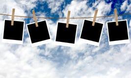 Polaroid- foto's die op een kabel met wasknijpers hangen Stock Afbeelding